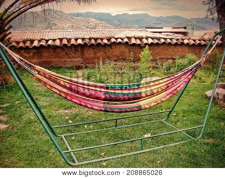 View of the hanging hammock of colored fabric standing in the garden and hung on a special metal structure
