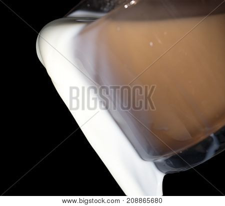 milk in a glass on a black background