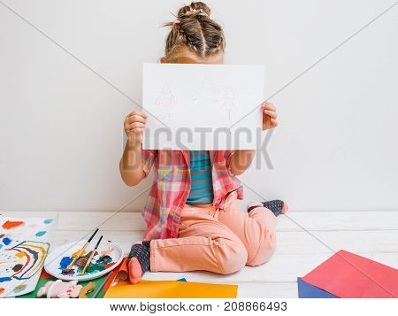 Uncertain artist. Shy baby girl. Unconfident kid paint work, white background. Early childhood education, shyness concept