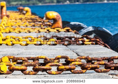 Harbor, sea holidays. Chains. Summer season, yellow chains mooring in a port. Background with infinite chains, tires, blue sea.