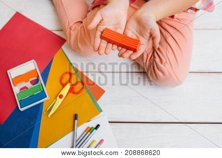 Artistic creation. Early child education. Unrecognizable creative girl top view in focus on foreground. Artwork on white background with free space, creativity concept