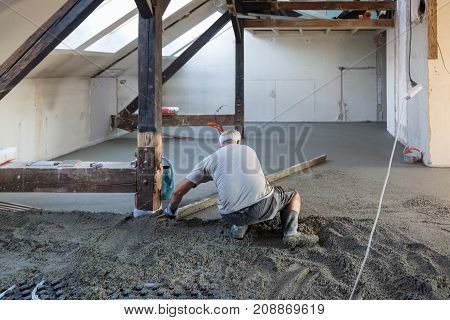 Laborer leveling sand and cement screed over floor heating. Sand and cement floor screed.