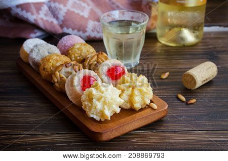 Panellets different Catalan small cakes served with sweet white wine . Typical sweets consumed at All Saints Day Dia Todos Los Santos in Catalonia Spain.