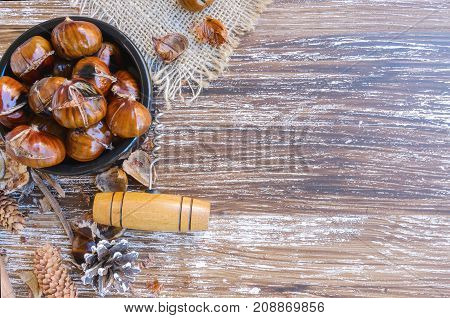 Tasty roasted chestnuts on ceramic bow vintage corkscrew and natural cones on wooden rustic table. Festive winter holiday treats background. Top view.Copy space.