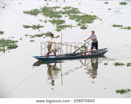 Kaiping Guangdong China, 28 October 2014: Asian fisherman couple with fishing net on small boat on a river with beautiful water at sunrise in rural China