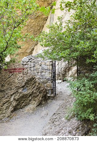 An open gate on the path. Travel along the coast along the path of Prince Golitsyn.