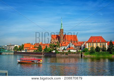 Wroclaw/Poland- August 18, 2017: View of Church of Holy Cross and St. Bartholomew on Tumski Island, Odra river with touristic boat, blue sky, summer.