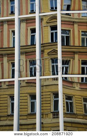 Distorted old building of Praga as reflected in modern windows