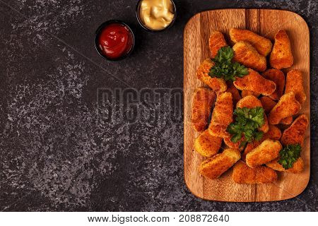 Chicken nuggets with sauces on dark background top view.