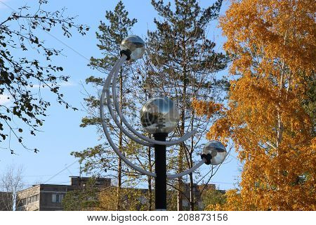 Oak with golden foliage and green larch on a background of blue sky / Autumn landscape in a park / Urban landscape with autumn trees and a street lamp