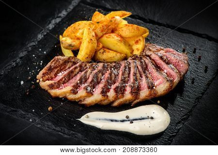 Minced meat barbecued stakes served with fried potatoes and bowls of sauces on black dish