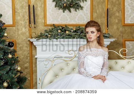 Beautiful young bride with wedding makeup and hairstyle in bedroom newlywed woman final preparation for wedding. Happy Bride waiting groom. Marriage Wedding day moment. Bride portrait soft focus