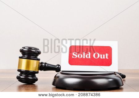 Business auction concept. Wooden gavel and sold out tag in wood room.