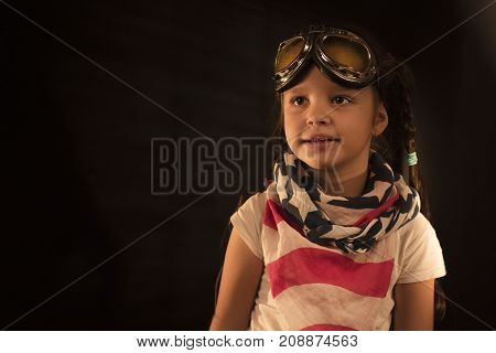 Child is pretending to be a pilot. Kid in studio. Superhero, freedom and imagination concept