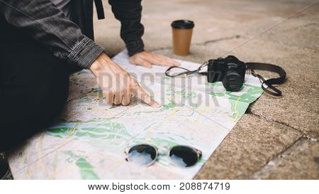 Cut view of a young man that has found a place on the map he wants to visit. This man is sitting on thr concrete ground while the map is laying on it. Also there are a cup of coffee, glasses and small blck camera on the map. Close up