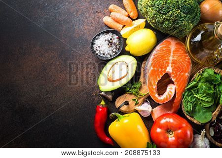 Balanced diet food background. Organic food for healthy nutrition superfoods. Meat fish legumes nuts seeds greens oil and vegetables. Top view copy space on dark stone table.
