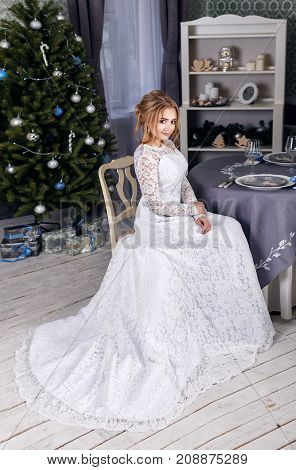 Bride in beautiful dress sitting on chair indoors in white studio interior like at home. Trendy wedding style shot. Young attractive multi-racial Asian Caucasian model like a bride tender looking.
