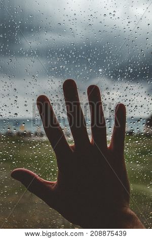 Silhouette of a hand touching a window full of water drops with cloudy sky in the background
