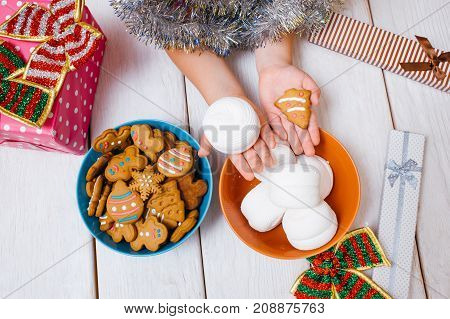 Miracle for child. Christmas festive food. Favorite time of year, unrecognizable kid with tasty sweets on wooden background. Yummy presents top view, joyful mood, meal concept