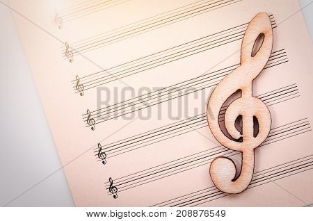 Creative musical concept wooden clef on blank sheet music notes.