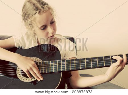 Little girl learns how to play guitar.