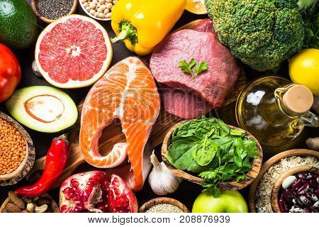 Superfood background. Organic food for healthy nutrition. Meat fish legumes nuts seeds greens oil and vegetables. Top view.