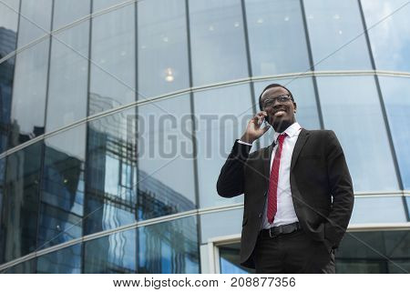 Outdoor Portrait Of Optimistic Dark-skinned Entrepreneur Standing In City Center In Black Suit, Whit