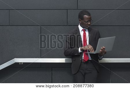 Horizontal Closeup Of Handsome African Businessman Standing In Street Against Gray Wall Background,