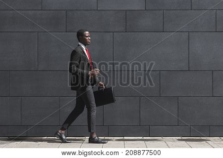 Full-length Portrait Of Handsome African American Entrepreneur Walking On Pavement With Gray Block W