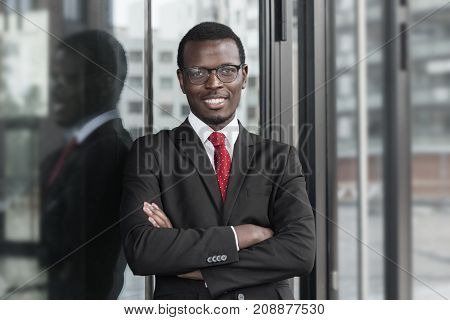 Indoor Closeup Of Handsome African Company Leader Wearing Dark Suit, White Shirt And Tie, Looking St