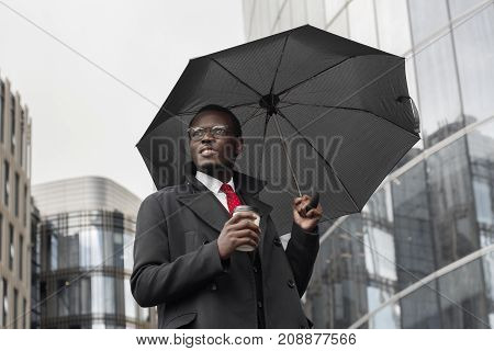 Street Portrait Of Young Handsome African American Businessman Standing In City Center In Dull Weath