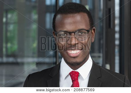 Horizontal Headshot Of Handsome Dark-skinned Businessman With Glass Background Behind, Spending Time