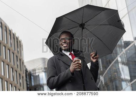Horizontal Image Of Dark-skinned African Entrepreneur Walking Under Dark Umbrella Along Busy Street
