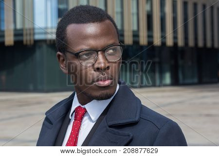 Horizontal Headshot Of Dark-skinned African Entrepreneur Standing In Street Standing Against High Bu