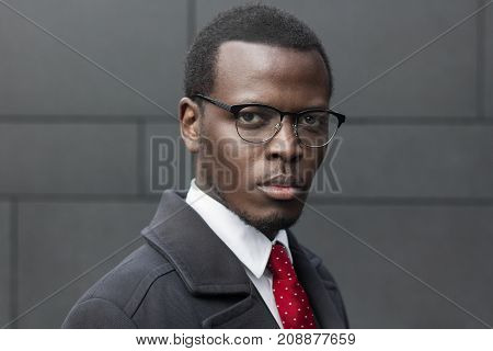 Horizontal Headshot Of African American Entrepreneur Standing Isolated Against Dark Grey Wall, Dress