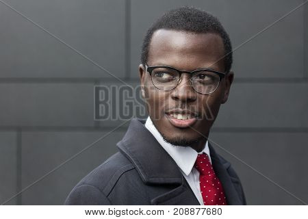 Horizontal Closeup Of African American Businessman Standing Isolated Against Dark Grey Wall, Dressed