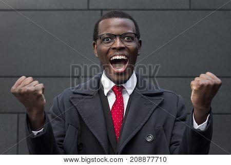 Horizontal Headshot Of Dark-skinned Businessman Wearing Warm Coat Standing With Gray Brick Wall Behi