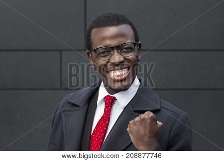 Horizontal Closeup Of African American Businessman Pictured Against Gray Wall In Formal Clothes And