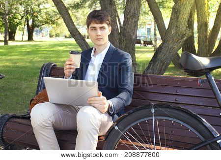Businessman on a coffee break. He is sitting on a bench and working at laptop, next to bike