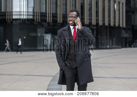Outdoor Image Of Young African American Man Moving From One Office To Another, Standing In Street In