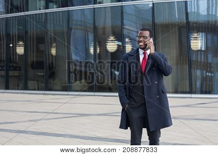 Horizontal Photo Of Young Dark-skinned African Businessman Standing In Street In City Center With Gl