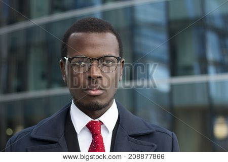 Urban Headshot Of Handsome African Businessman Dressed In Smart Coat In City Street Wearing Stylish