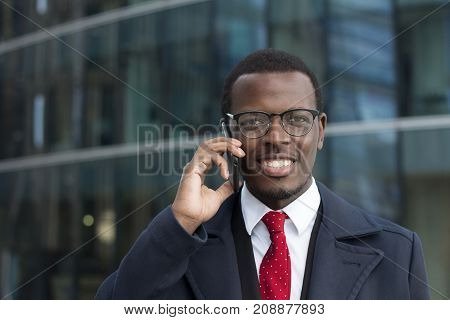 Outdoor Headshot Of African American Businessman Talking On Phone In Street Discussing Important Bus
