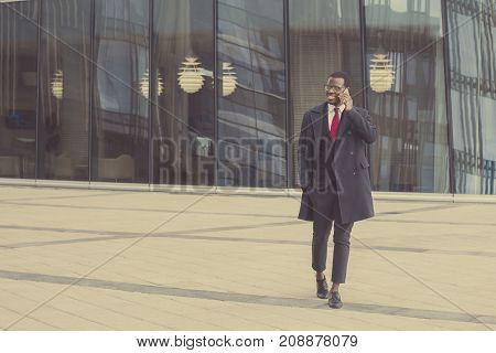 Full-length Portrait Of Young African American Entrepreneur Walking On Pavement With Gray Street Wal