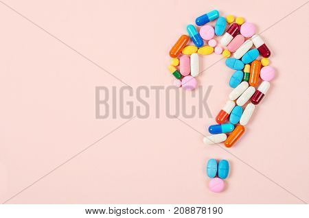 Question mark made of lots of pills and capsules on color background.