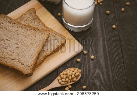 Breakfast with soy beans in spoon soy milk and sandwich on wooden background