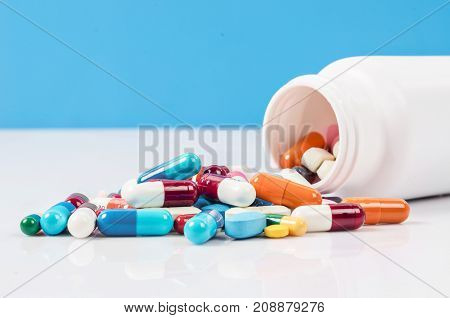Pill bottle with pill spill isolated on blue background.