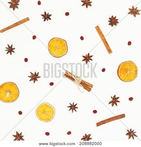 Pattern of cinnamon, anise and dried oranges on white background. Flat lay, top view. Christmas or New Year concept.