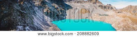 Panorama of beautiful mountain lake with turquoise water and rocky mountains