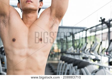 Young Man Execute Exercise With Machine In Fitness Center. Male Athlete Training In Gym. Sporty Guy